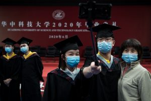 Huazhong University of Science and Technology (HUST) holds annual graduation ceremony in Guanggu Stadium, with around 300 graduates being on site, and thousands of students witness the ceremony online, and take photos with classmates through tablets, Wuhan City, central China's Hubei province, 21 June 2020 (Reuters).