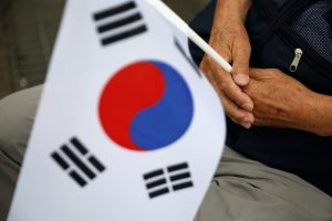 A South Korean war veteran holds the national flag during a ceremony commemorating the 70th anniversary of the Korean War, near the demilitarized zone separating the two Koreas, in Cheorwon, South Korea, 25 June, 2020 (Photo: Reuters/Hong-Ji).