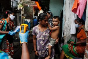 A healthcare worker checks the temperature of residents of a slum area using an electronic thermometer during a check-up campaign for the coronavirus disease (COVID-19), in Mumbai, India, 6 July 2020. (Photo: Reuters/Francis Mascarenhas).