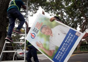 Workers hang up electoral poster for ruling People's Action Party ahead of the general election in Singapore, 30 June 2020 (Photo: Reuters/Edgar Su).
