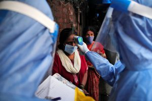 A healthcare worker checks the temperature of a woman using an electronic thermometer during a check up campaign for the coronavirus disease (COVID-19) at a slum area in Mumbai, India 8 July, 2020 (Photo:Reuters/Francis Mascarenhas).
