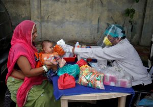 A doctor wearing a protective face shield uses an infrared thermometer to measure the temperature of a child at his mobile health clinic, after his clinic and its adjoining areas were declared a micro-containment zone, after authorities eased lockdown restrictions that were imposed to slow the spread of the coronavirus disease (COVID-19), in Ahmedabad, India, 15 June 15 2020 (Reuters/Amit Dave/File Photo).
