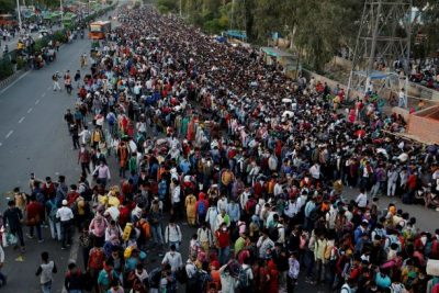 Migrant workers crowd up outside a bus station as they wait to board buses to return to their villages during a 21-day nationwide lockdown to limit the spreading of coronavirus disease (COVID-19), in Ghaziabad, on the outskirts of New Delhi, India, 28 March 2020 (Photo: Reuters/Anushree Fadnavis).